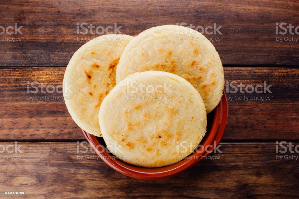 Plate with arepas on a rustic wooden background stock photo