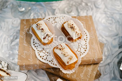 992836992 istock photo Plate with cakes decorated dessert table for a party. Delicious sweets on buffet. Table with muffins, candy for a party goodies on wedding banquet area. Close up. candy bar. flat lay. top view. 1132126374