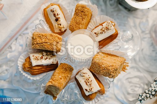 992836992 istock photo Plate with cakes decorated dessert table for a party. Delicious sweets on buffet. Table with muffins, candy for a party goodies on wedding banquet area. Close up. candy bar. flat lay. top view. 1132126393