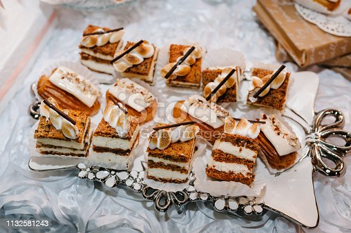 992836992 istock photo Plate with cakes decorated dessert table for a party. Delicious sweets on buffet. Table with muffins, candy for a party goodies on wedding banquet area. Close up. candy bar. flat lay. top view. 1132581243