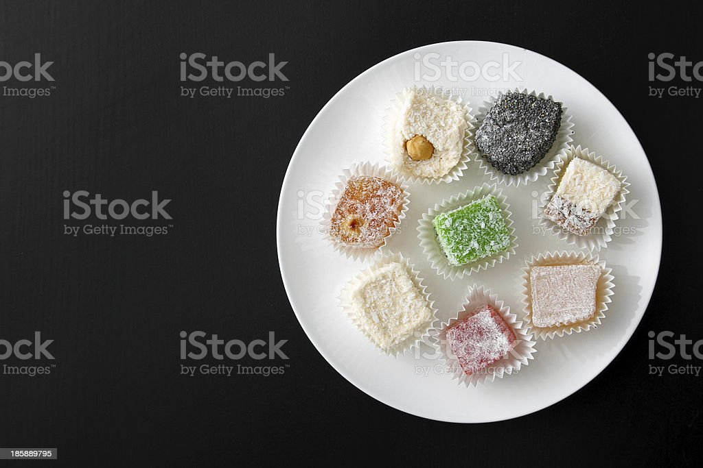 plate with colorful candies on dark table royalty-free stock photo
