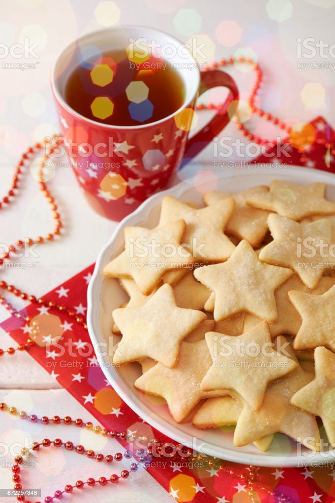 Plate with cookies shaped like star, cup of tea, christmas decorations stock photo