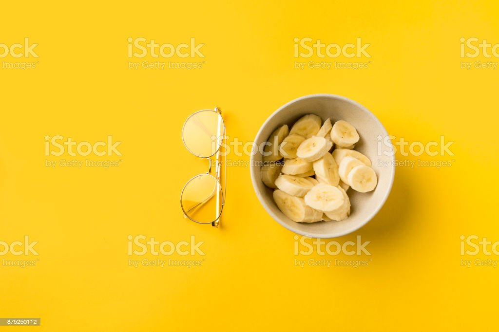 Plate with cut bananas and glasses stock photo
