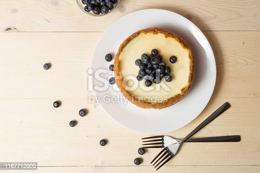 Plate with delicious cheesecake and two forks on wooden table