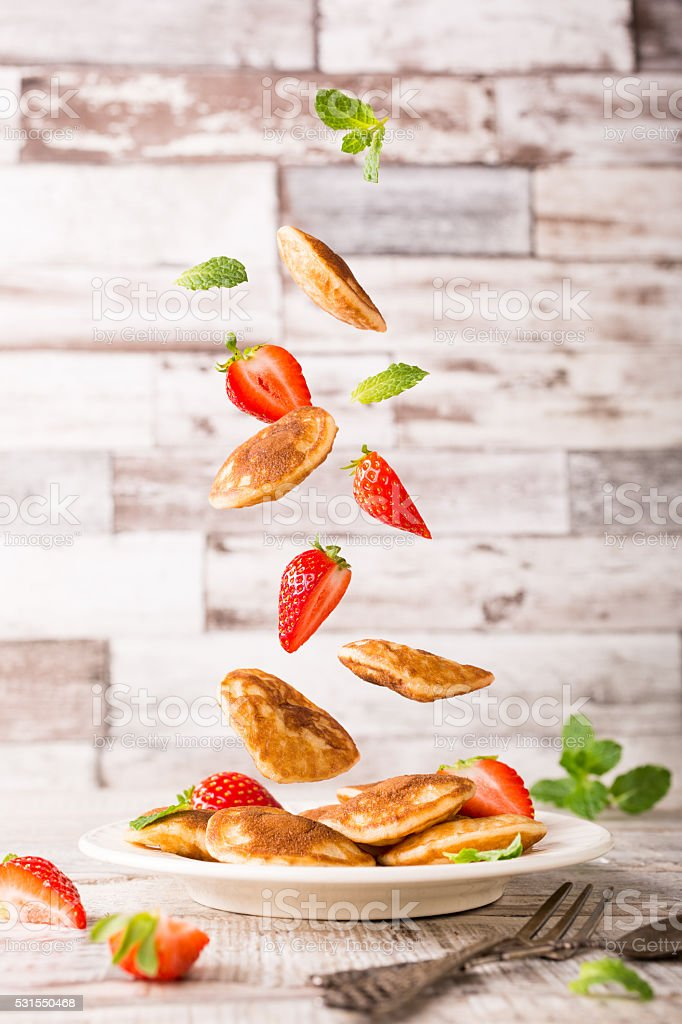 Plate with dutch mini pancakes called poffertjes and flying ingredients stock photo