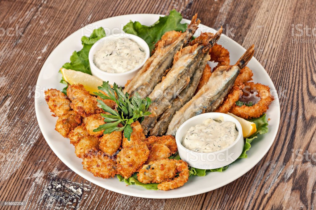 Plate with fish snack with white sauce and greens.