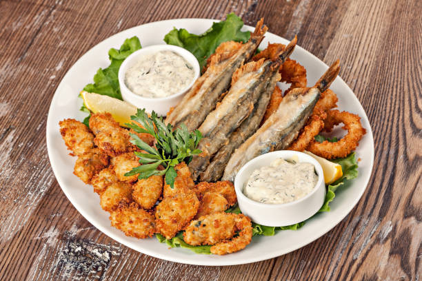 Plate with fish snack with white sauce and greens. stock photo