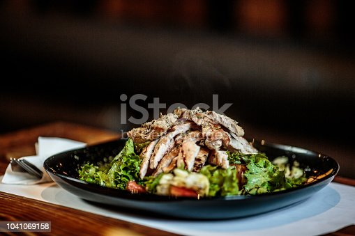 Close up view of a plate with delicious meat salad on the table.