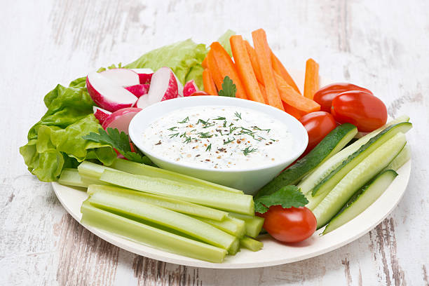 plate with fresh vegetables and thick yoghurt sauce stock photo