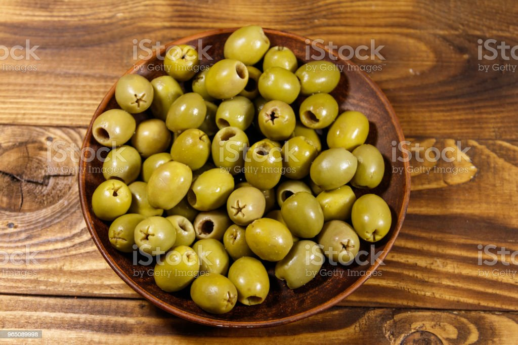 Plate with green olives on wooden table royalty-free stock photo