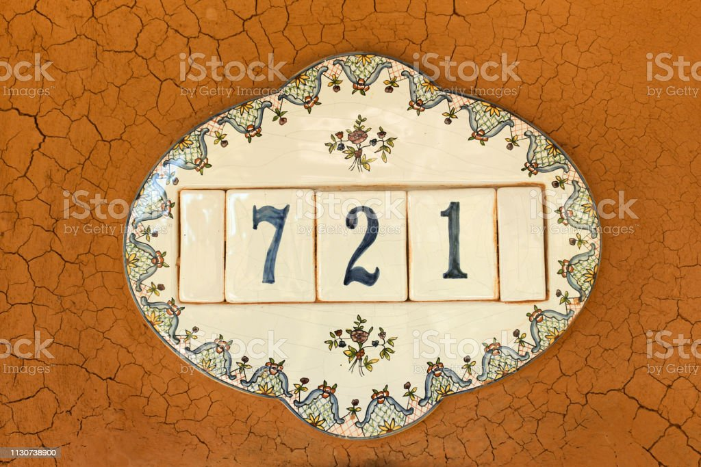 Plate with house number with mud wall. stock photo