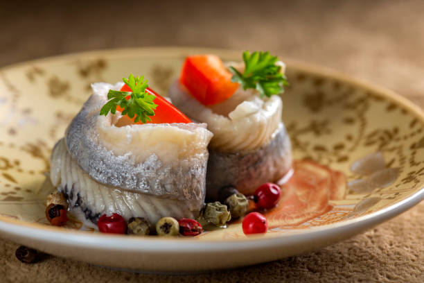 Plate with marina marinated herring fish with vegetables and herbs stock photo