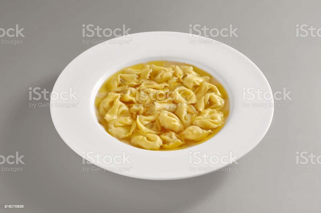 Plate with portion of tortellini pasta in broth stock photo