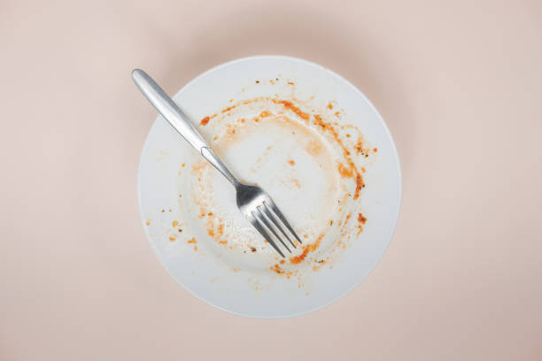 A plate with rests of tomato sauce in it, top view. stock photo
