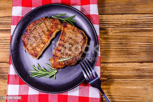 655794674 istock photo Plate with roasted steaks and rosemary twigs on a wooden table. Top view 1203815095