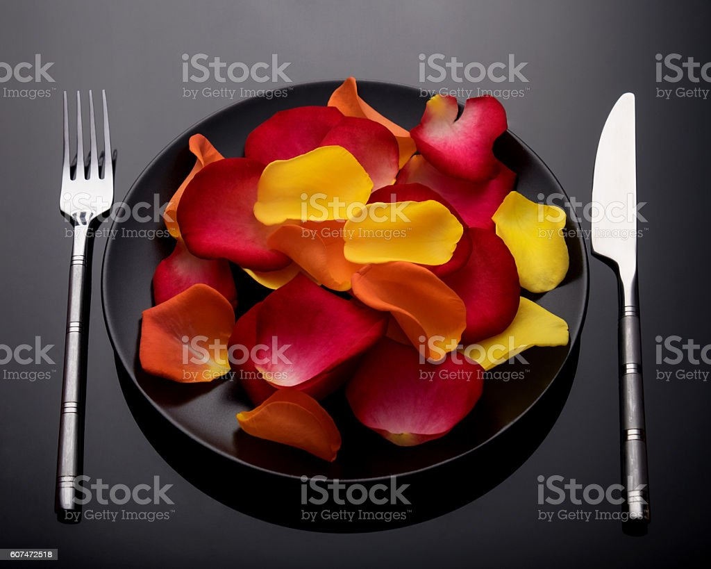 Plate with rose petals, fork and knife stock photo