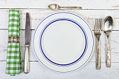 plate with silver cutlery on an old white table