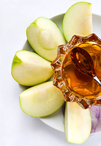 A plate with sliced apples and honey on it  Apples with honey rosh hashanah stock pictures, royalty-free photos & images