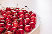 Plate with sweet cherries closeup. Freshly harvested summer berry in white bowl. Vitamin containing ripe fruits. Raw food ingredient, vegetarian diet component. Bio, eco, organic farming produce