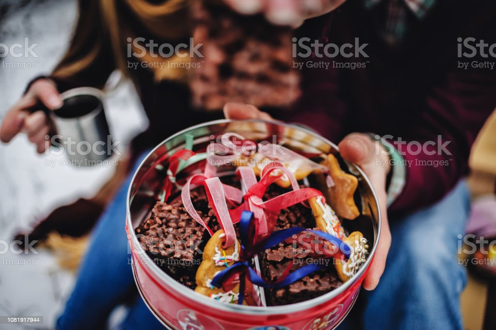 Plate With Tasty Christmas Cookies Gingerbread On Snowy Background In Man And Girl Hands Holiday Celebration And Cooking Concept Happy New Year And