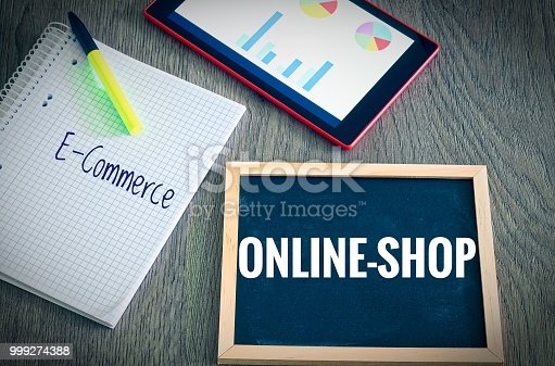 istock Plate with the inscription Webshop and E-Commerce with a tablet Graphs and statistics and block to illustrate the increase in sales of an online shop 999274388