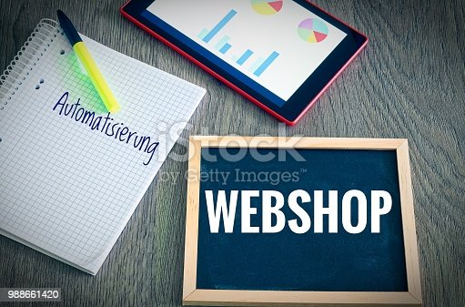 istock Plate with the inscription Webshop and the german Word Automatisierung in english automation with a tablet Graphs and statistics and block to illustrate the increase in sales of an online shop 988661420