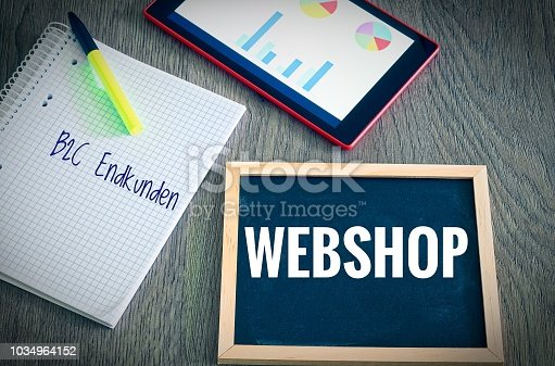 istock Plate with the inscription Webshop and the german Words B2C Endkunden in english B2C end customers (Business to consumer) with a tablet Graphs and statistics and block to illustrate the increase in sales of an online shop 1034964152