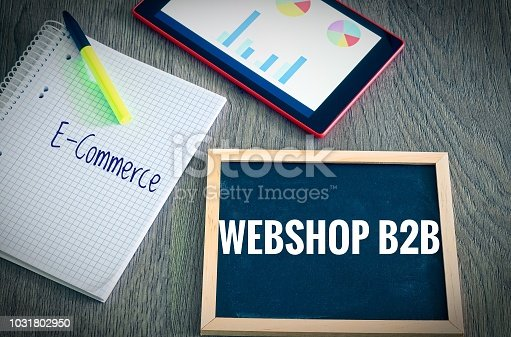 istock Plate with the inscription Webshop B2B (Business to Business) and E-Commerce  with a tablet Graphs and statistics and block to illustrate the increase in sales of an online shop 1031802950