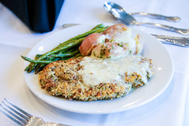 Plated food breaded chicken potatoes and asparagus silverware stock photo