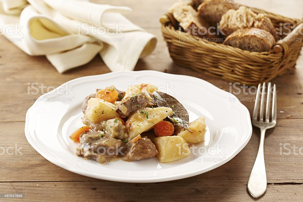 A plated serving of beef stew with a bread basket and napkin stock photo