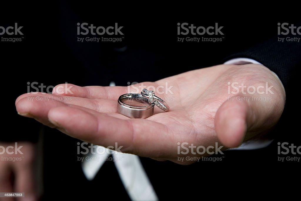 Platenum Wedding Rings in the groom's palm royalty-free stock photo