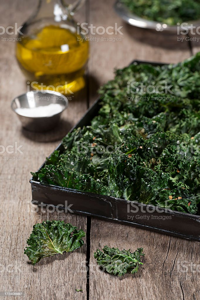 A plater of kale chips on a table with olive oil and salt  royalty-free stock photo