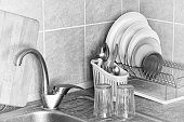 Washed plates, cutlery and glasses, drying in their racks close to the sink in the kitchen