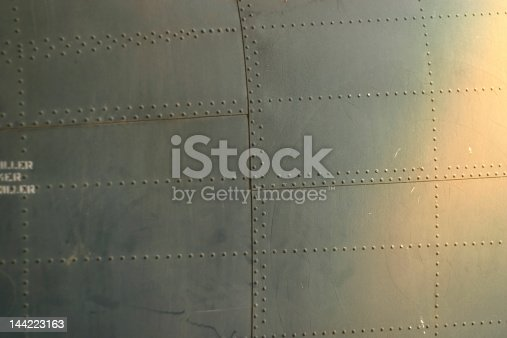 Plated part of an old airplane, steel and rivets.