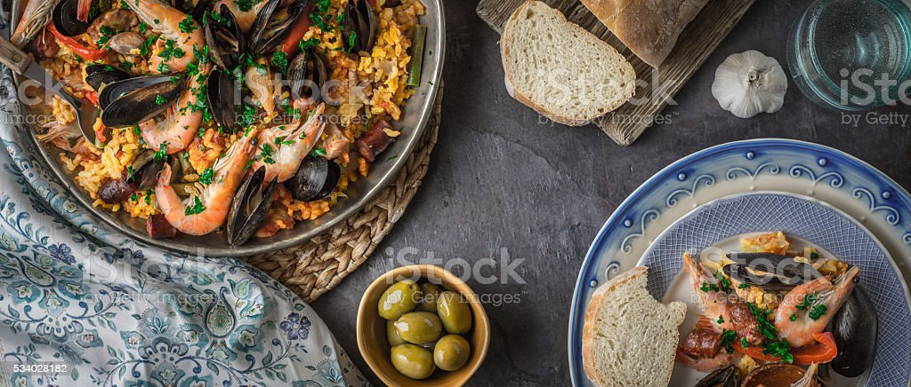 Plates with paella on stone table with  accessories wide screen – Foto