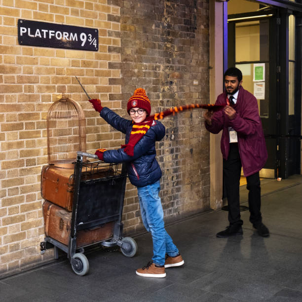 Platform 9 3/4 in London, UK London, UK - December 30, 2018: Visitor posing at the Platform Nine and Three-Quarters, featured in the popular Harry Potter films, recreated at the London Kings Cross Railway Station railroad station platform stock pictures, royalty-free photos & images