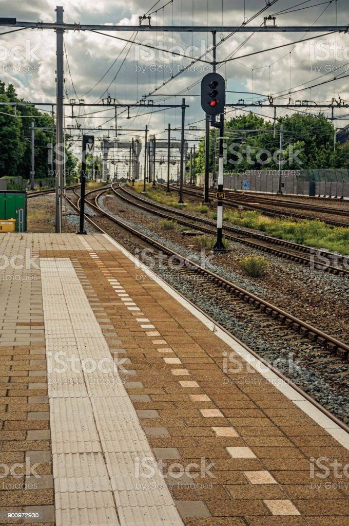 Platform, railroad rails and signaling at train station under blue cloudy sky at Weesp. stock photo