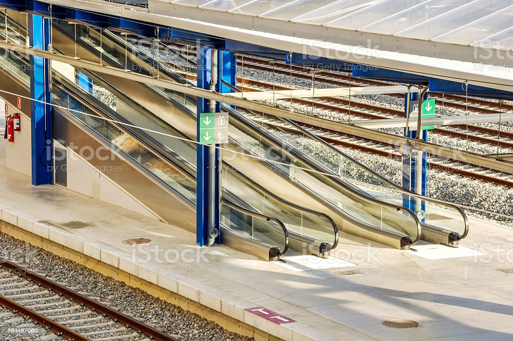Platforms of railway station with escalators and signposting. stock photo