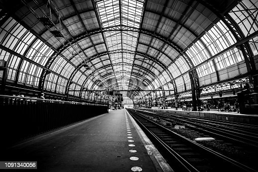 Platforms of the Amsterdam train station (Amsterdam Central Station - Centraal Station), Netherlands. Black and white image. Low key image
