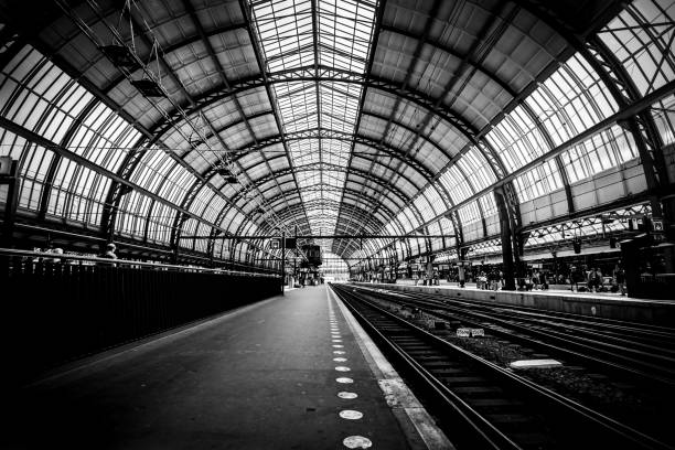 Platforms of the Amsterdam train station (Amsterdam Central Station - Centraal Station), Netherlands. Black and white image. Low key image Platforms of the Amsterdam train station (Amsterdam Central Station - Centraal Station), Netherlands. Black and white image. Low key image railroad station stock pictures, royalty-free photos & images