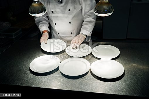 Chef laying out plates at the pass ready for service. Colour, horizontal with some copy space. Photographed in a restaurant on the island of Møn in Denmark.