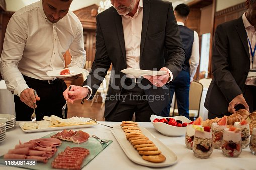 Business men plating up complimentary food while at a business conference.