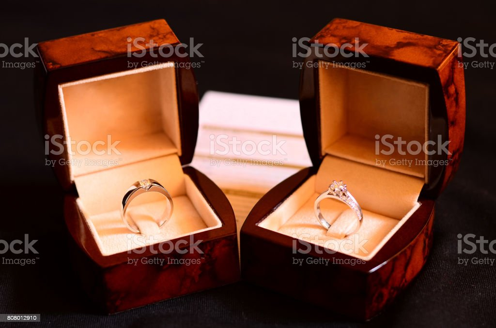 Platinum Diamond Ring, Wedding rings in a box on dark background with warranty card stock photo