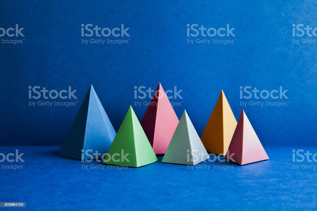 Platonic solid geometric figures. Three-dimensional pyramid rectangular objects on blue background. Yellow blue pink violet red colored tetrahedron abstract shapes objects stock photo