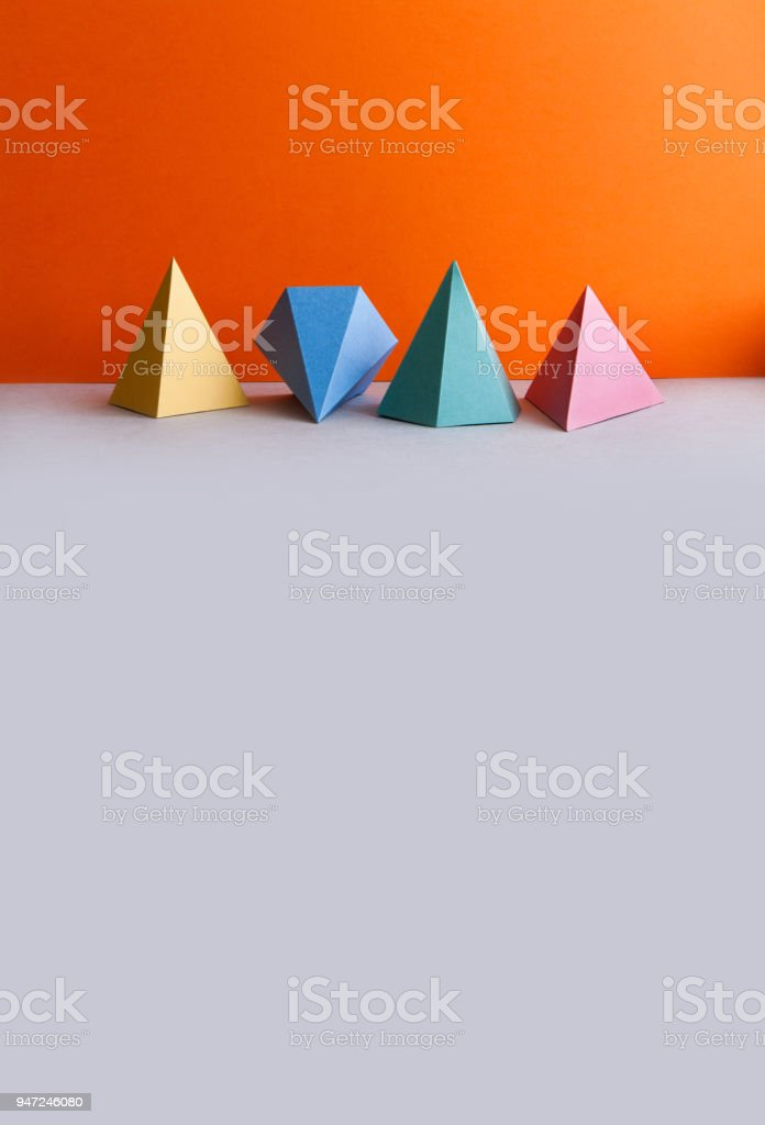 Platonic solid geometric figures. Three-dimensional pyramid rectangular triangle objects on orange gray background. Yellow blue red green colored tetrahedron abstract shapes objects. copy space stock photo