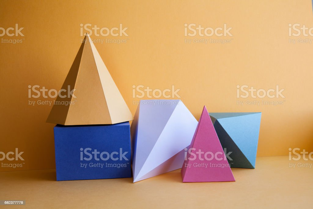 Platonic solids abstract still life composition. Prism pyramid rectangular cube figures on yellow paper background. Yellow blue white green color geometric objects royalty-free stock photo