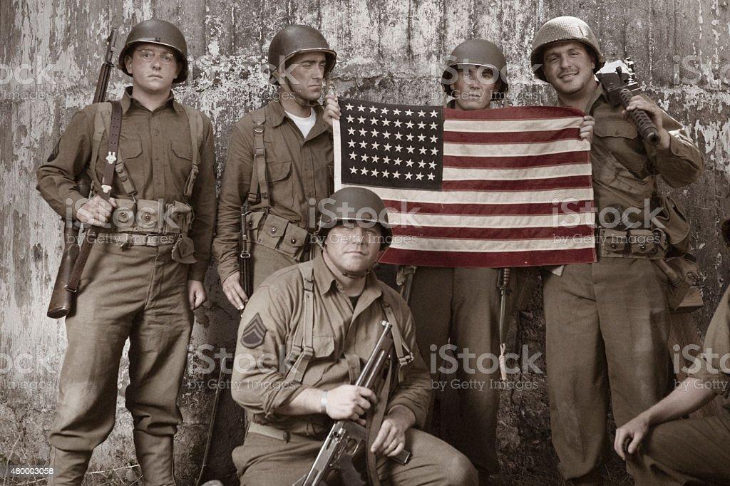 WW2 platoon holding American Flag stock photo