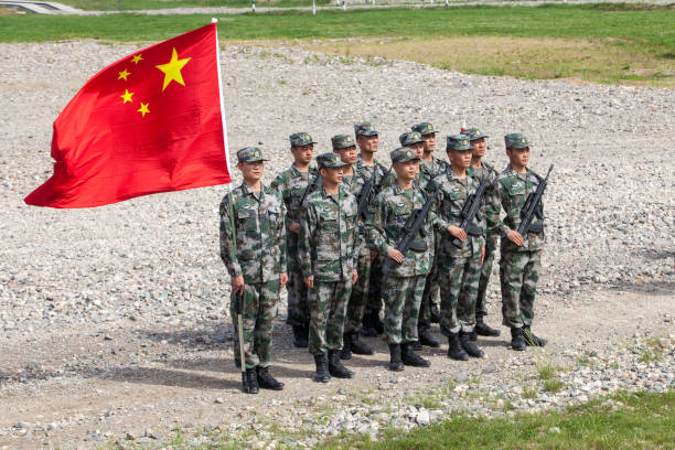 Platoon of Chinese soldiers with the flag of the Chinese People`s Republic Pesochnoye village, Kostroma region, Russia - June 10, 2018. Great military games Army Games 2018.  The country participants of the games Iran Kazakhstan Belarus China Armenia Russia Egypt  One of the stages is a safe environment (international competitions among military units of chemical and bacteriological protection)  a platoon of Chinese soldiers with the flag of the Chinese People`s Republic military parade stock pictures, royalty-free photos & images