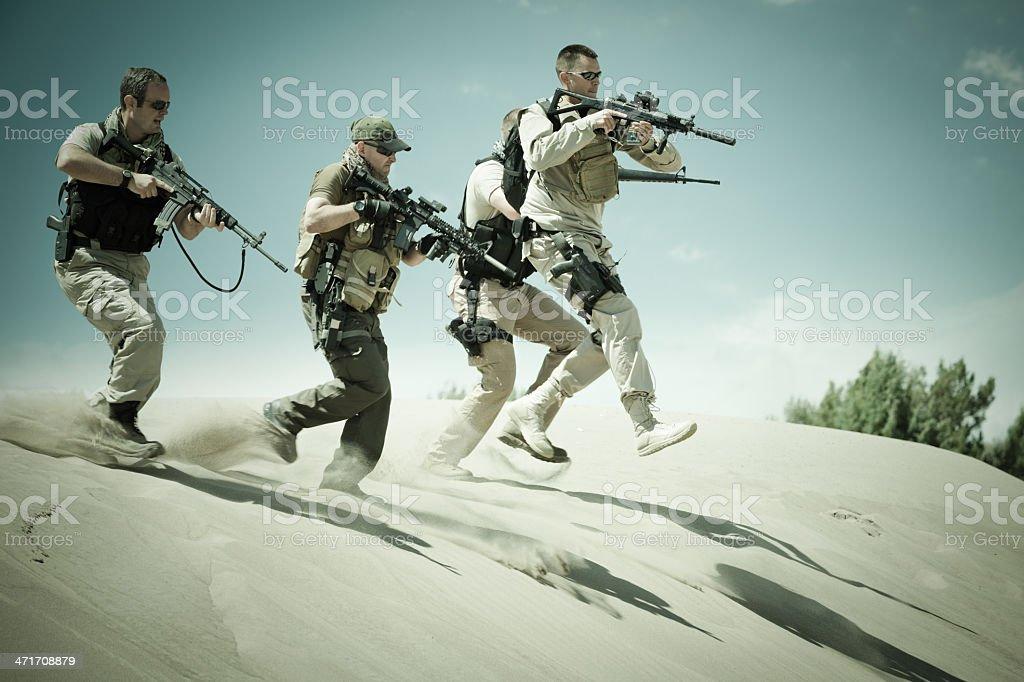 Platoon of military soldiers running through desert royalty-free stock photo