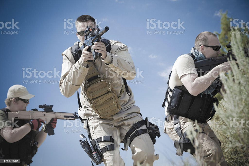 Platoon of military soldiers using weapons during training exercise stock photo